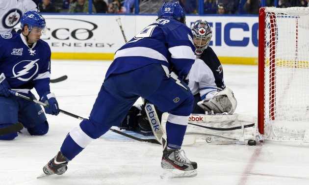 Winnipeg Jets goalie Montoya makes a save on Tampa Bay Lightning's Conacher during their NHL hockey game in Tampa, Florida