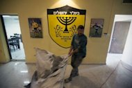An employee removes a bag of debris after a fire broke out at the Beitar Jerusalem football club in Jerusalem on February 8, 2013. The torching of Beitar Jerusalem's offices by fans angry at the signing of two Muslim players has sparked a major outcry which both supporters and ex-players hope could end decades of open racism at the club