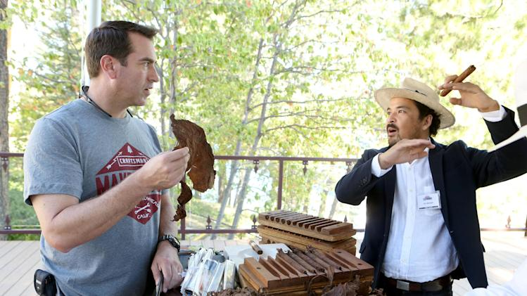 "IMAGE DISTRIBUTED FOR CRAFTSMAN - EXCLUSIVE - Actor and comedian Rob Riggle, left, examines tobacco leaves with cigar-rolling expert Taz Ahmadi at the Craftsman MAKEcation on Sat., Aug. 30, 2014, in Lake Arrowhead, Calif. The Craftsman MAKEcation is the ultimate ""making"" vacation where attendees learn skills from hardcore blacksmiths, rugged woodworkers and a survival guru. Visit Twitter.com/Craftsman to follow the event in real time. (Photo by Casey Rodgers/Invision for Craftsman/AP Images)"