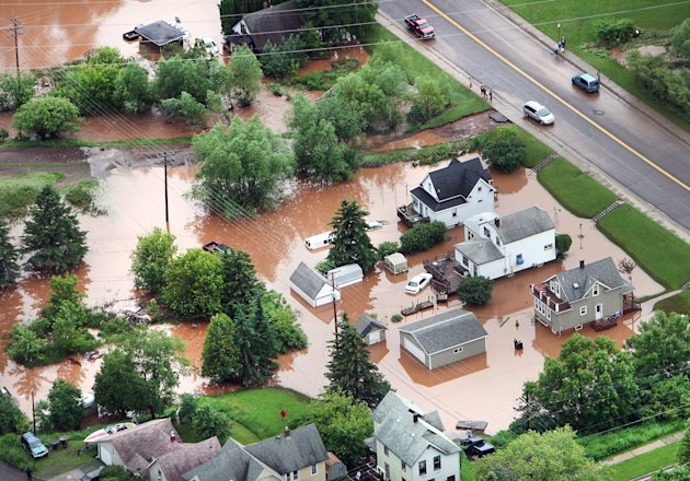 In this aerial photo, waters from an overflowing nearby creek inundate homes in the Irving Park neighborhood of Duluth, Minn., Wednesday afternoon, June 20, 2012. Residents evacuated their homes and animals escaped from pens at a zoo as floods fed by a steady torrential downpour struck northeastern Minnesota, inundating the city of Duluth, officials said Wednesday. (AP Photo/The Duluth News-Tribune, Bob King)
