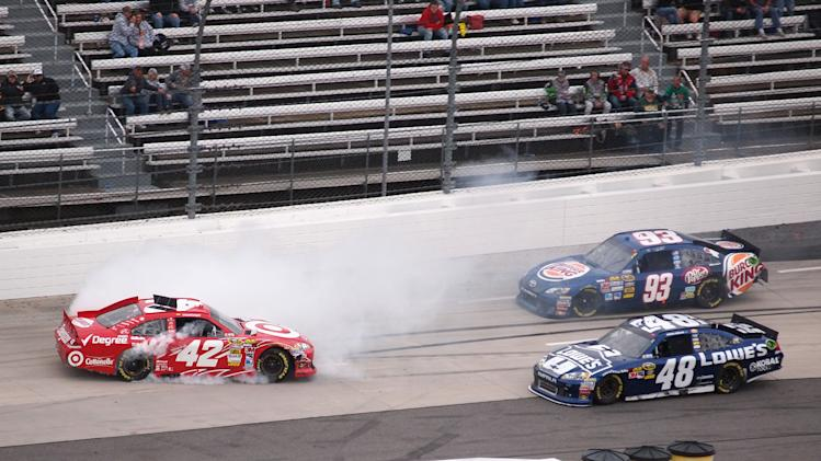 Juan Pablo Montoya (42) spins in front of Jimmie Johnson (48) during the NASCAR Sprint Cup Series auto race at Martinsville Speedway, Sunday, Oct. 28, 2012, in Martinsville, Va. (AP Photo/Steve Sheppard)