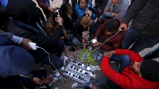 Stranded migrants charge their phones on a field with electricity provided by a generator at the Greek-Macedonian border near the Greek village of Idomeni