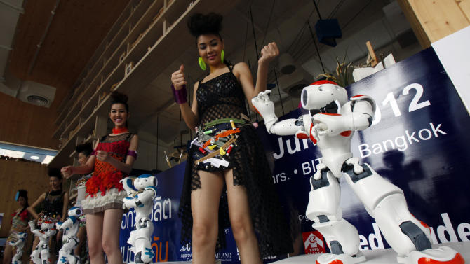 "Models dance with the humanoid robot ""NAO"" during a news conference in Bangkok"