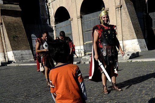 A child looks at men dressed up as gladiators in front of Rome's Colosseum in June