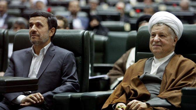 FILE - In this Sunday, May 27, 2012, file photo, former Iranian President Akbar Hashemi Rafsanjani, right, smiles, as he sits next to President Mahmoud Ahmadinejad, in an inauguration ceremony of the parliament in Tehran, Iran. Hashemi Rafsanjani, Iran's influential former president, says his country is not at war with archenemy Israel, the media reported Monday, in the latest departure by a high-profile politician from the strident anti-Israel line traditionally taken by many senior Iranian leaders. The remarks by Akbar Hashemi Rafsanjani follows calls from figures across the political spectrum to repair the damage to Iran's international reputation they said had been caused by outgoing President Mahmoud Ahmadinejad, who called Israel a doomed state and questioned the extent of the Holocaust. (AP Photo/Vahid Salemi, File)