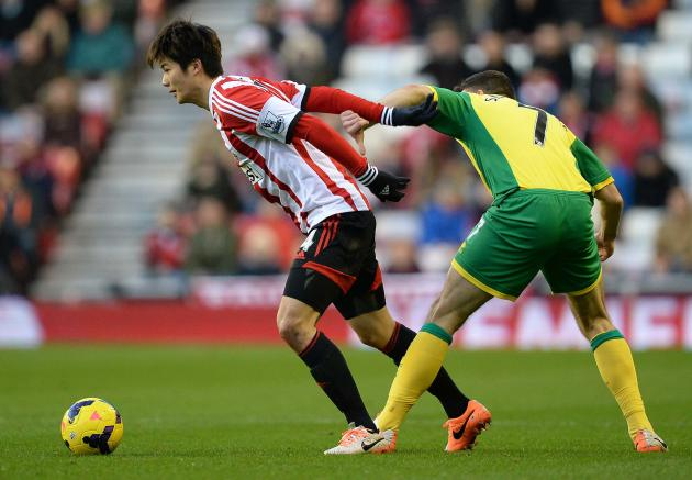 Norwich City's Snodgrass challenges Sunderland's Ki during English Premier League soccer match at The Stadium of Light in Sunderland