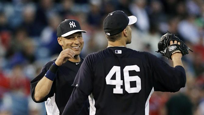 New York Yankees shortstop Derek Jeter (2) talks to Yankees starting pitcher Andy Pettitte (46) during a spring training baseball game against the Philadelphia Phillies in Tampa, Fla., Wednesday, March 13, 2013.  (AP Photo/Kathy Willens)