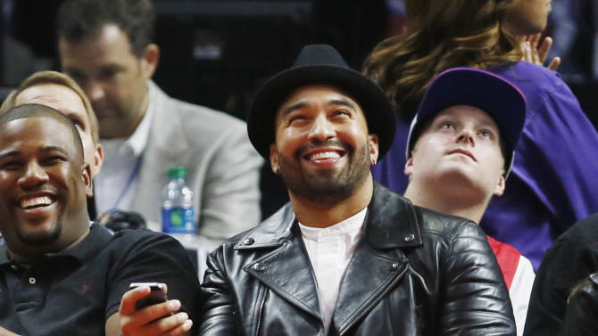 Major League Baseball player Matt Kemp of the San Diego Padres smiles as the crowd reacts to him being shown on the scoreboard screen during the first half of an NBA basketball game between the Los Angeles Clippers and Milwaukee Bucks Saturday, Dec. 20, 2014, in Los Angeles. (AP Photo/Danny Moloshok)