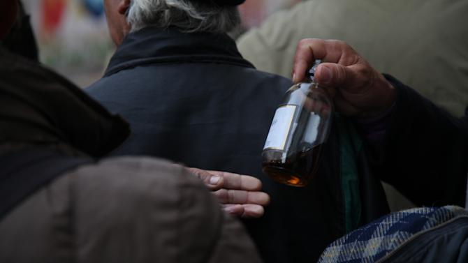 In this May 29, 2013 photo, men share a drink before entering a homeless shelter, where their liquor would be confiscated, at the indoor stadium Estadio Victor Jara in Santiago, Chile. In the stadium that served as a torture facility 40 years ago, Santiago's most marginalized population can sleep indoors during Chile's biting winter. (AP Photo/Brittany Peterson)