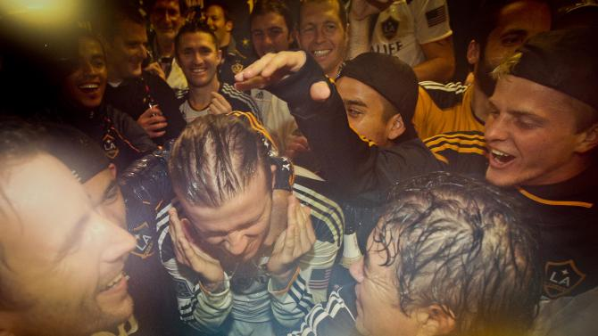 Los Angeles Galaxy midfielder David Beckham, center left, celebrates with his teammates after the Galaxy defeated the Houston Dynamo in the MLS Cup championship soccer match, Sunday, Nov. 20, 2011, in Carson, Calif. (AP Photo/Bret Hartman)