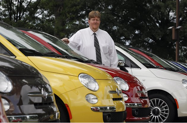 In this Tuesday, May 8, 2012, photo, James Tharp sales manger at Fiat of South Atlanta in Morrow, Ga., poses with new Fiats Tuesday May 8, 2012. Back when gas was cheap, Americans bought cars with V-8