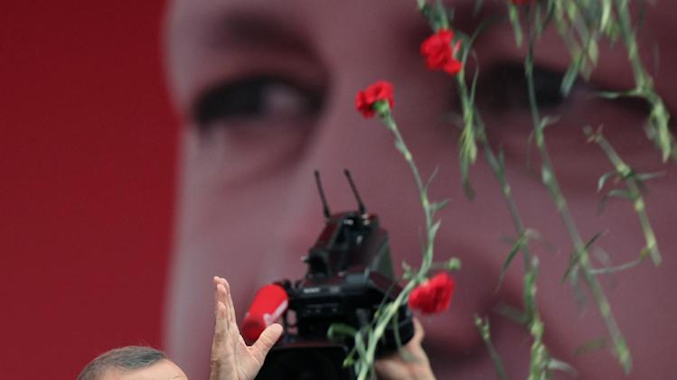 Turkish Prime Minister Recep Tayyip Erdogan throws carnations toward supporters during a party rally outside Ankara, Turkey, Saturday, June 15, 2013. Erdogan said Friday he has asked a small delegation of protesters to convince those occupying a park to withdraw, adding that he is hopeful their protest action would end soon.(AP Photo/Burhan Ozbilici)