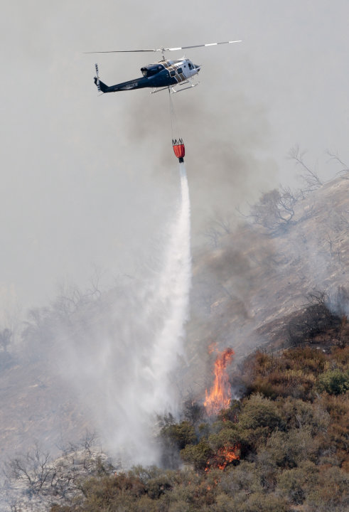 A firefighting helicopter drops water on a wildfire in the Angeles National Forest north of Glendora, Calif. Monday, Sept. 3, 2012. A day after the wildfire broke out near a campground and forced the