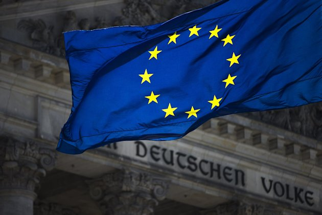 A European flag waves in front of the Reichstag building with the inscription 'Dem deutschen Volke' ('To The German People') in Berlin, Germany, Thursday, Aug. 23, 2012. Official data show that Germany posted a budget surplus for the first half of this year thanks to its strong labor market, even as other eurozone countries struggle with deficits. (AP Photo/Markus Schreiber)