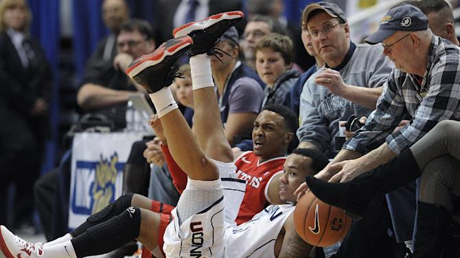 FILE - In this Jan. 27, 2013, file photo, Rutgers' Myles Mack, rear, reacts as he is called for traveling after falling into fans with Connecticut's Shabazz Napier, front, during the second half of an NCAA college basketball game in Hartford, Conn. Oklahoma State All-American guard Marcus Smart is serving a three-game suspension for shoving a fan who later apologized for his actions. The incident shows how volatile the interaction between fans and athletes is becoming. (AP Photo/Jessica Hill, File)