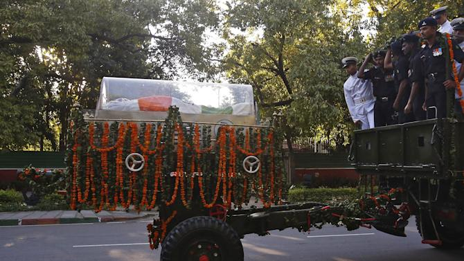 Indian soldiers escort a gun carriage carrying the body of former Indian President Kalam in New Delhi