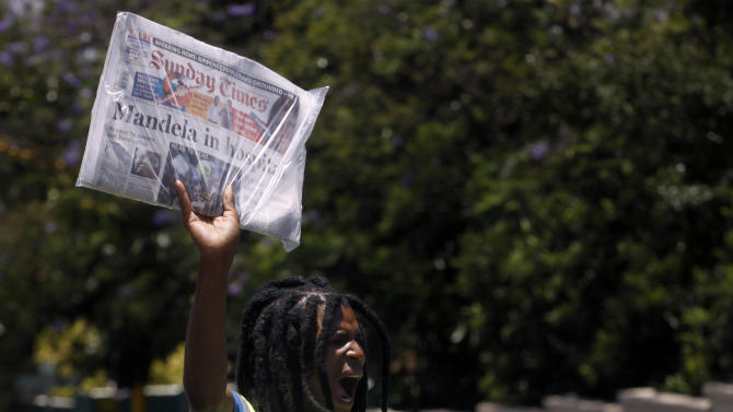 "A newspaper vendor sells Sunday newspapers reporting on former South African President, Nelson Mandela, in Johannesburg Sunday Dec. 9, 2012. South Africans prayed Sunday for the health of former President Nelson Mandela and anxiously awaited further word about the anti-apartheid leader after he was admitted to a military hospital. President Jacob Zuma visited Mandela Sunday morning at the hospital in Pretoria and found the frail 94-year-old to be ""comfortable and in good care,"" presidential spokesman Mac Maharaj said in a statement. Maharaj offered no other details about Mandela, nor what medical tests he had undergone since entering the hospital Saturday.  (AP Photo/Denis Farrell)"
