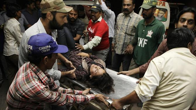 People rush an injured woman to an emergency ward of a local hospital in Karachi, Pakistan  on Wednesday, Nov. 21, 2012. Two bombs exploded outside a Shiite mosque in the southern city of Karachi, killing scores of people and wounding others in a suicide attack, police official said. (AP Photo/Fareed Khan)