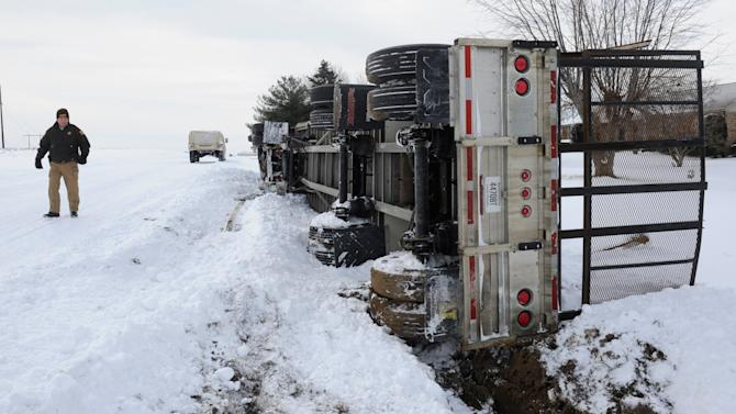 While out on patrol in a humvee, Henderson County Deputy Sheriff Warren Weiss inspects a semi-tractor trailer that overturned Thursday, March 5, 2015, on U.S. 41A in Henderson County, Ky.  Kentucky Gov. Steve Beshear has declared a state of emergency for the second time in less than a month. (AP Photo/The Gleaner, Mike Lawrence)