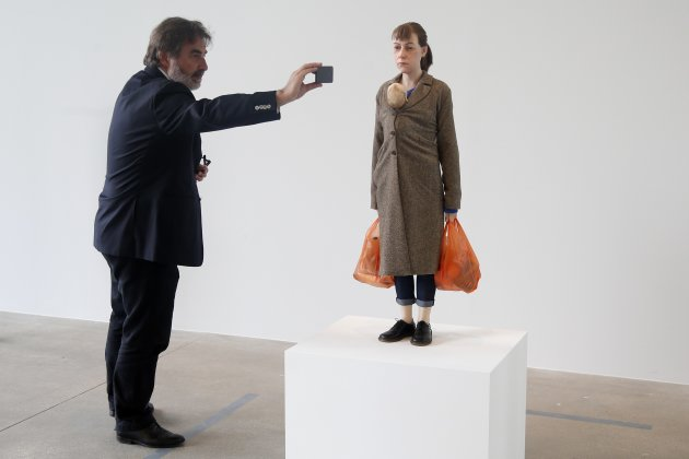 "A visitor takes a picture of a sculpture entitled ""woman with Shopping, 2013"" by artist Ron Mueck during his exhibition at the Fondation Cartier pour l'art contemporain in Paris"