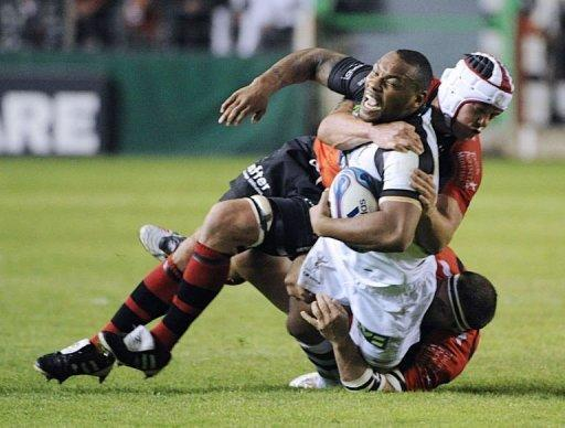 Harlequins' Matt Hopper is tackled by Toulon's Johan Christiaan Van Niekerk (helmet) and Mike Brown