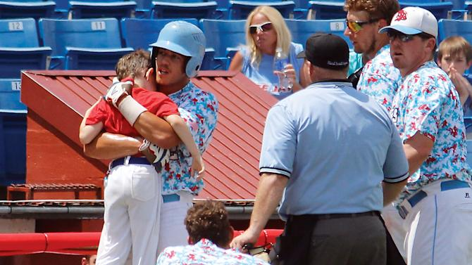 In this Aug. 1, 2015,  photo, Liberal's Gavin Wehby holds Bee Jays batboy Kaiser Carlile moments after the 9-year-old was accidentally hit in the head during a National Baseball Congress World Series game in Wichita, Kan. Kaiser, who was wearing a helmet, was struck by a follow-through swing near the on-deck circle. He died on Sunday. (Earl Watt/Leader & Times via AP) MANDATORY CREDIT