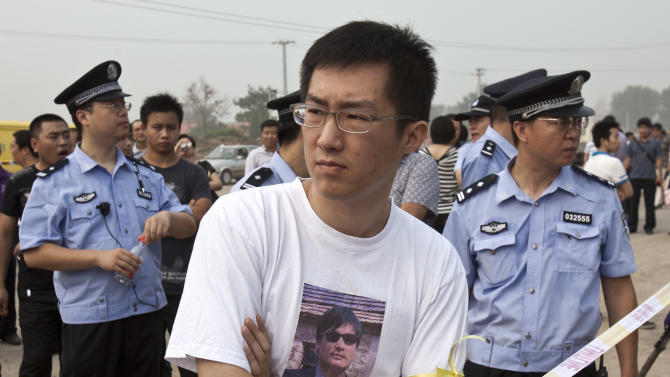 Qi Jianxiang, son of Wang Lihong, center, is surrounded by policemen as he waits to enter Wenyuhe People's Court in Beijing, China, Friday, Aug. 12, 2011. Wang, a Chinese activist known for pushing legal issues and backing a jailed Nobel peace laureate went on trial Friday on a vaguely worded charge, reinforcing Beijing's sweeping crackdown on dissent. (AP Photo/Andy Wong)