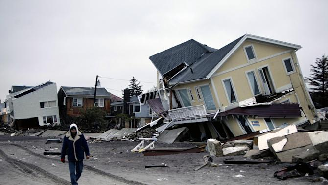 In this Tuesday, Nov. 27, 2012 file photo, a man walks past destroyed homes on the Rockaway Peninsula in Queens, New York. Delegates from nearly 200 countries are meeting in the Qatari capital of Doha to discuss ways slowing climate change, including by cutting emissions of greenhouse gases that scientists say are warming the planet, melting ice caps, raising sea levels, and changing rainfall patterns with impacts on floods and droughts (AP Photo/Seth Wenig, File)