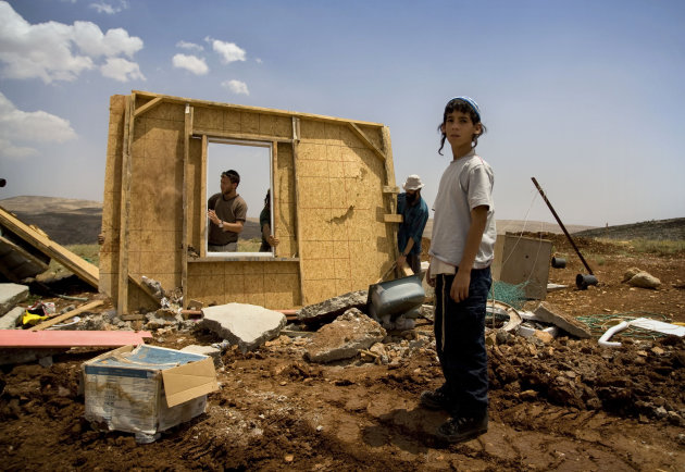 FILE - In this May 21, 2009 file photo Jewish settlers try to rebuild a structure demolished earlier by Israeli troops in the West Bank outpost of Maoz Esther, a hilltop site northeast of Ramallah. A government-appointed committee is recommending that Israel legalize dozens of unauthorized West Bank settlement outposts. Committee member Alan Baker said Monday, July 9, 2012 the panel believes Israel has the right to settle the West Bank because the territory is not occupied.(AP Photo/Sebastian Scheiner, File)