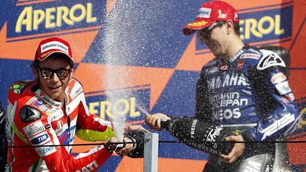 Ducati MotoGP rider Valentino Rossi of Italy (L) who placed second, and Yamaha MotoGP rider Jorge Lorenzo of Spain (R) who placed first, spray champagne on the podium at the end of the San Marino motorcycling Grand Prix at the Misano circuit (Reuters)