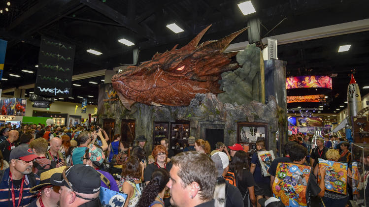 Fans walk past a Smaug the Dragon display during preview night at the 2014 Comic-Con International Convention held Wednesday, July 23, 2014 in San Diego. (Photo by Denis Poroy/Invision/AP)