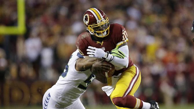 Seattle Seahawks outside linebacker Leroy Hill stops Washington Redskins quarterback Robert Griffin III during the first half of an NFL wild card playoff football game in Landover, Md., Sunday, Jan. 6, 2013. (AP Photo/Evan Vucci)