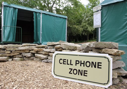 In this photo taken Wednesday, May 22, 2013, a cell phone zone located near a digital hub, left, and concession stand are shown at Muirfield Village Golf Club in Dublin, Ohio. The cell phone zones wer