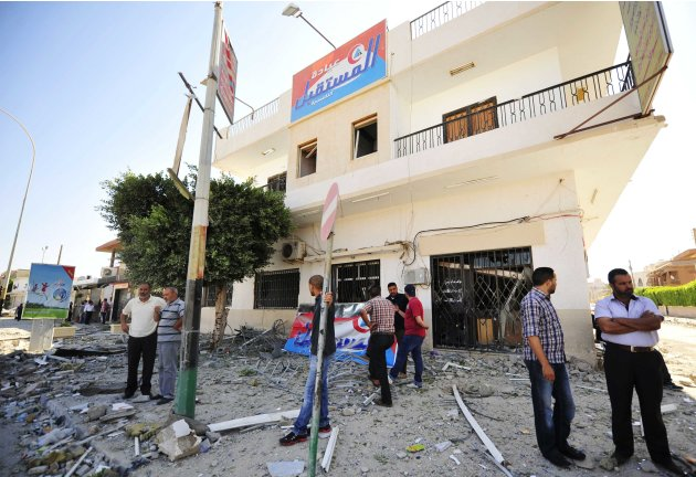 People stand in front of a clinic damaged by the impact of a bomb explosion nearby at a police station in Benghazi