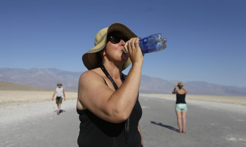 Maria Wieser, of Italy, takes a drink of water while sightseeing in Death Vally National Park, Friday, June 28, 2013 in Badwater, Calif. Excessive heat warnings will continue for much of the Desert Southwest as building high pressure triggers major warming in eastern California, Nevada, and Arizona. (AP Photo/Chris Carlson)