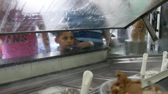 A Palestinian boy waits to buy ice-cream in Gaza City on a hot summer day, Thursday, July 19, 2012. Muslims from Morocco to Afghanistan are steeling themselves for the toughest Ramadan in more than three decades. They're asked to refrain from food and drink, even a sip of water, for 14 hours a day during the hottest time of the year, a test of self-restraint made harder by daily power cuts in some parts of the Muslim world, such as Iraq, Pakistan and tiny Gaza. (AP Photo/Adel Hana)