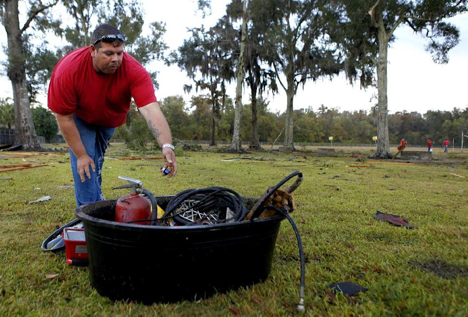 Terrebonne Parish Trustee Michael Buquet, 34, cleans up storm debris left by strong winds from a suspected tornado Wednesday, Nov. 16, 2011 at Village East School in Houma, La.   No one was injured. (AP Photo/The Houma Courier, Julia Rendleman)