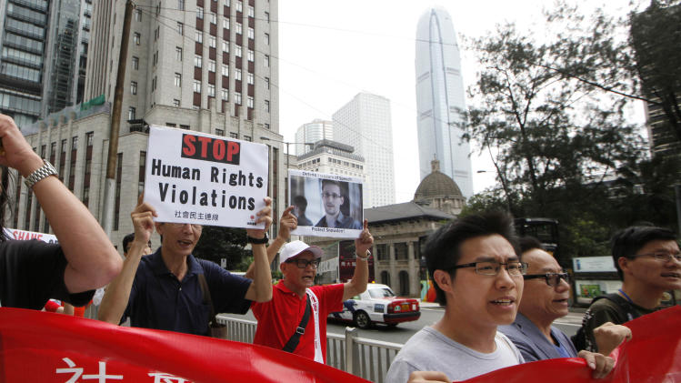 Demonstrators hold signs supporting Edward Snowden, who leaked top-secret information about U.S. surveillance programs, outside the U.S. Consulate General in Hong Kong Thursday, June 13, 2013 as they demand that U.S. government should make public the targeted people and institution in Hong Kong and apologize to those who are targeted. The news of Snowden's whereabouts, revealed by an editor of a local newspaper that interviewed him Wednesday, is the first since he went to ground Monday after checking out of his hotel in this autonomous Chinese territory. (AP Photo/Kin Cheung)