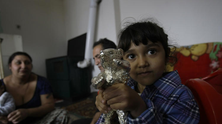 Sandra Mujic, the daughter of the unexpected  movie star, Nazif Mujic, plays with her favorite toy - her dad's best actor award, the Silver Bear  in the living room o their home in the village of Poljice, 150 kms northeast of Sarajevo, on Wednesday, April 10, 2013.  People in the Gypsy village  of Poljice say they will never forget the night they almost fell off their chairs two months ago. Did they really hear the elegant woman on TV correctly? Could she really be talking about their neighbor, the toothless man who passed his days selling scrap metal and lived in the shack down the road? The camera switched to a frightened-looking Najif Mujic. Yes it was him. THEIR Nazif _ who had just left Matt Damon and Jude Law in the dust to win the best actor award at the Berlin Film Festival.    (AP Photo/Amel Emric)