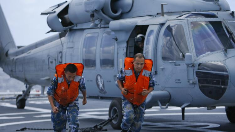 Sailors from Chinese PLA run after unhooking a U.S. Navy UH60 Seahawk as it prepares to take off from the PLA ship Peace Ark during the RIMPAC in Honolulu