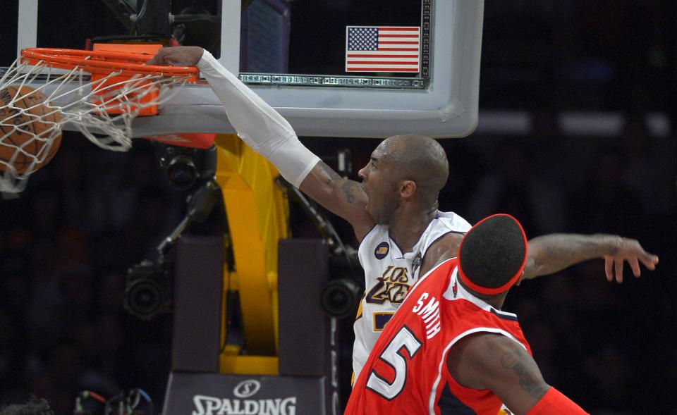 Los Angeles Lakers guard Kobe Bryant, right, dunks as Atlanta Hawks forward Josh Smith defends during the second half of their NBA basketball game, Sunday, March 3, 2013, in Los Angeles. The Lakers won 99-98. (AP Photo/Mark J. Terrill)