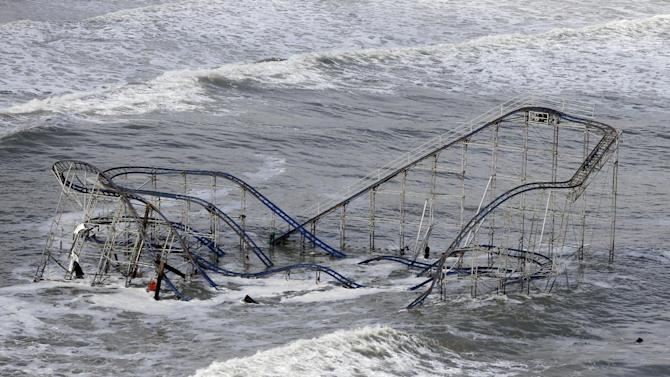 FILE - In this Wednesday, Oct. 31, 2012 file photo, waves wash over a roller coaster from a Seaside Heights, N.J. amusement park that fell in the Atlantic Ocean during Superstorm Sandy. Superstorm Sandy, the rare and devastating Northeast storm, and an election that gave Democrats gains have put global warming back in the picture. (AP Photo/Mike Groll)
