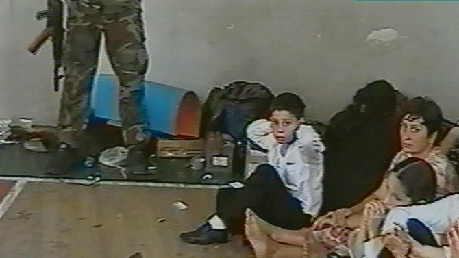 FILE - Hostages sit on a floor in a gym as a hostage-taker stands with his left foot on a book apparently with a device connected to a chain of explosives in the school in Beslan, Russia taken  in this undated image from television during the early part of the siege which began on  Sept. 1, 2004 and ended with over 300 people dead. Two suspects in the Boston Marathon bombing have been identified to The Associated Press as coming from a Russian region near Chechnya  In the past, insurgents from Chechnya and neighboring restive provinces in the Caucasus have been involved in terror attacks in Moscow and other places in Russia. (AP Photo/NTV-Russian Television Channel, File)