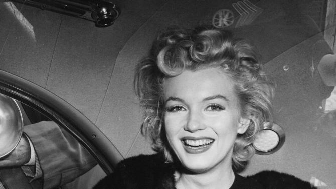 """FILE - In this June 2, unknown year, file photo, actress Marilyn Monroe smiles in a car after arriving tousled from an all-night plane flight from Hollywood to Idlewild Airport, in New York. She said she planned to rest in New York before going to England to make a new movie with Sir Laurence Olivier. Sidestepping questions as to whether she and playwright Arthur Miller plan to wed, she said: """"No comment, we're really good friends."""" (AP Photo, File)"""