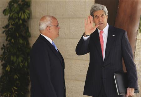 U.S. Secretary of State Kerry waves as he stands next to Palestinian Chief Negotiator Erekat in Ramallah