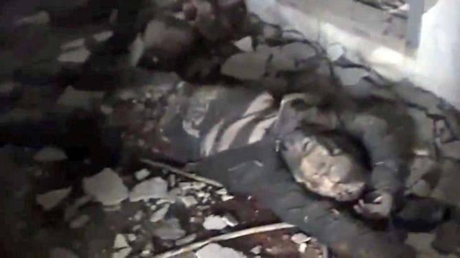 In this Sunday March 3, 2013 image taken from video obtained from the Shaam News Network, which has been authenticated based on its contents and other AP reporting, a dead Syrian government soldiers lies within the police academy complex in Khan al-Asal, in the province of Aleppo, Syria. The Britain-based Syrian Observatory for Human Rights said the rebels seized the police academy in Khan al-Asal after entering the sprawling government complex with captured tanks. The Observatory said the battle left at least 120 soldiers and 80 rebels dead. (AP Photo/Shaam News Network via AP video)