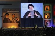 Lebanon's Hezbollah leader Sayyed Hassan Nasrallah addresses his supporters via a screen during a ceremony to mark the death of Hezbollah commander Hasan al-Laqqis, in Beirut's southern suburbs December 20, 2013. REUTERS/ Sharif Karim