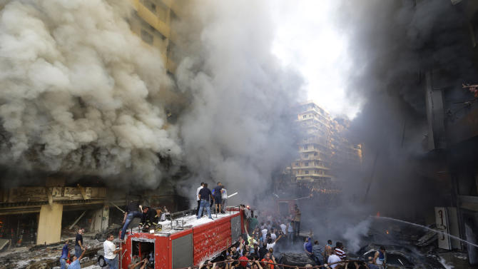 Lebanese citizens and Hezbollah supporters gather at the scene of a car bomb explosion in southern Beirut, Lebanon, Thursday Aug. 15, 2013. The powerful car bomb ripped through a southern Beirut neighborhood that is a stronghold of the militant group Hezbollah on Thursday, killing at least three people and trapping others in burning buildings, the media said. (AP Photo/Hussein Malla)