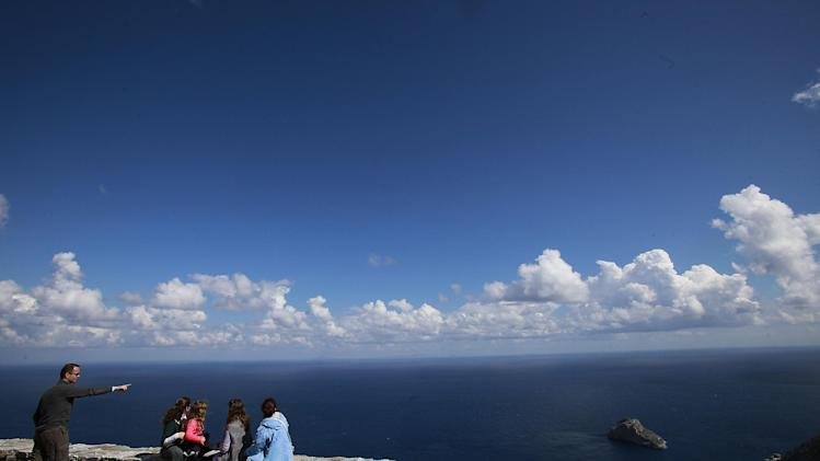 Tourists admire the Aegean see from the top of the village of Hora, in the Greek island of Amorgos on Friday April 18, 2014. (AP Photo/Dimitri Messinis)