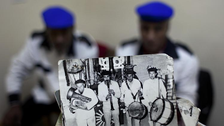 "In this Thursday, Jan. 10, 2013 photo, Egyptian musician and drum player Ezzat el-Fayoumi, 65, the last member of one of Egypt's oldest and best known percussion music bands, called Hassaballah, holds a photo of the original band with him in it, at right, among his late team mates while performing at a theater in 1975, in Cairo, Egypt. During its heyday,  Mohammed Ali street was famed as the lively and romantic heart of Arabic music and home to musicians, belly-dancers and instrument makers. ""The street is extinct,"" el-Fayoumi said, sitting at a coffee shop that now serves as his office. ""When I die, there will be no more music. No one is learning it."" (AP Photo/Nasser Nasser)"